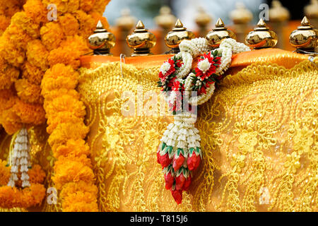 Thai luxury craft garland handmade hang on to pagoda barricade covered by yellow gold cloth. - Stock Photo