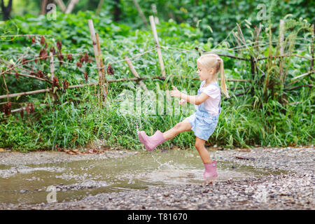 Child in a pink rubber boots in the rain jumping in puddles. Kid playing in summer park - Stock Photo