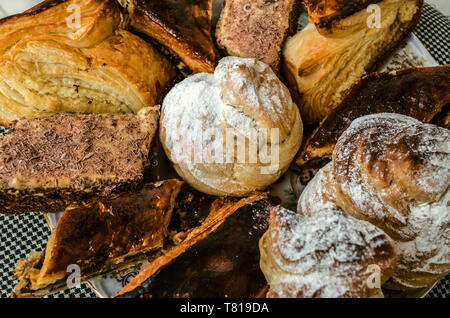 Traditional Armenian biscuit 'Gata' and baklava of puff pastry, pieces of various cakes and eclairs on a porcelain plate - Stock Photo