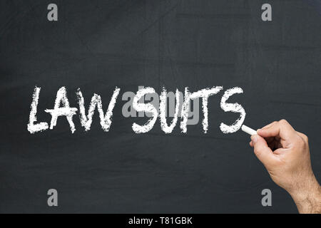 Male's hand writing text on the chalkboard: Law suits - Stock Photo