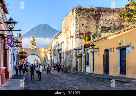 Antigua, Guatemala - April 14, 2019: Street with Santa Catalina Arch, ruins & Agua volcano behind in colonial town & UNESCO World Heritage Site. - Stock Photo