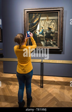 Rear view of a young woman taking a photo of the Art Of Painting by Jan Vermeer inside the Kunsthistorisches Museum in Vienna, Austria. - Stock Photo