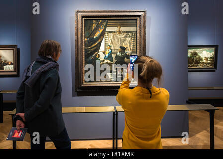 Rear view of two tourists looking at the Art Of Painting by Jan Vermeer inside the Kunsthistorisches Museum in Vienna, Austria. - Stock Photo
