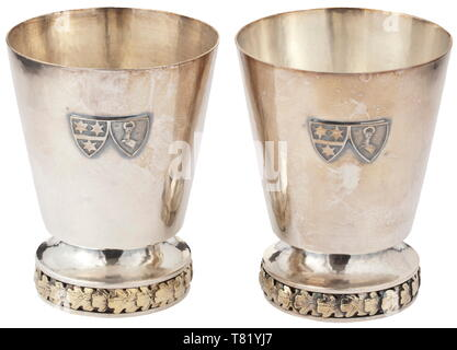 Hermann and Emmy Göring - two silver drinking beakers from their personal table service. Heavy wrought issue, the lower edges with a continuous frieze of oak leaves in relief, the viewing surfaces with an applied alliance coat of arms. The bottom with the master's mark of Prof. Herbert Zeitner, Berlin, Göring's preferred gold- and silversmith. Fineness 925. Height 11 cm. Weight 285 g and 305 g. Eminently beautiful, heavy silversmith work. Provenance: Keith Wilson Collection, Kansas City. historic, historical, 20th century, 1930s, NS, National Socialism, Nazism, Third Reich,, Editorial-Use-Only - Stock Photo