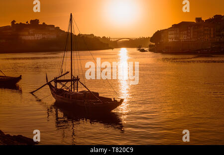 Porto at sunset: Duoro river with rabelo boat in front of setting sun and Arrabida bridge in background, Portugal - Stock Photo