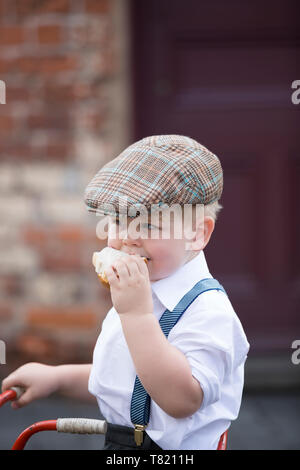 Close up of cute little boy in 1940's costume wearing flat cap & braces isolated outdoors, eating big jam sandwich, Black Country Museum, WWII event. - Stock Photo