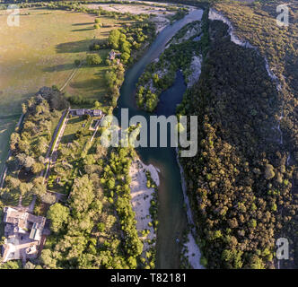 Stunning aerial drone shot of the Rhone river at sunrise. The river reflects the early morning sun and the river gorge is forested and green. - Stock Photo