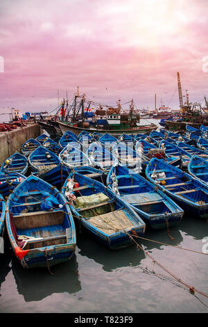Scenic landscape with blue wooden fishing boats in the foreground in the port of Essaouira, Morocco during sunset - Stock Photo