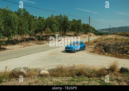 Car stop on a countryside dirt road in rocky landscape with trees near Monsanto. A cute and peculiar historic village of Portugal. - Stock Photo