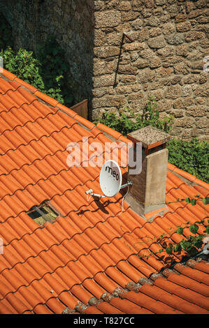 House roof with parabolic antenna stuck in chimney on a sunny day at Monsanto. A cute and peculiar historic village of Portugal. - Stock Photo