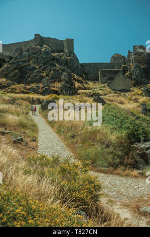 People walking up stone path towards castle on top of rocky hill covered by flowers near Monsanto. A cute and peculiar historic village of Portugal. - Stock Photo
