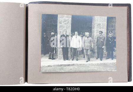 Hermann Göring - A photo album of Mussolini's official visit to Carinhall Large format photo album (34 x 24 cm) with brown leather cover with gold-embossed 'MUSSOLINI BEI GOERING IN KARINHALL', '28 SEPTEMBER 1937' and 'BILDBERICHT VON CARLO CARLETTI'. Album consists of eighteen 17 x 23 cm black and white photos. Photos are of a casual/informal style and feature Hermann Göring, Emma Göring, Mussolini, Count Ciano, Achille Starace, Luftwaffe Generals Milch, Stumpf, and Bodenschatz, Paul Schmidt, SS General Dietrich, and more. From the possession of a US officer of the 101st A, Editorial-Use-Only - Stock Photo