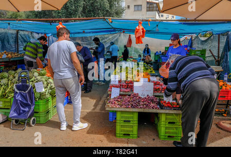 Limassol, Cyprus - March 23, 2019:  Outdoor fruit and vegetable farmer's market in Limassol, held on a Saturday.  Shows shoppers chosing their produce - Stock Photo