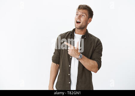 Impressed and excited attractive fair-haired european guy with bristle open mouth from fascination looking and pointing at upper left corner - Stock Photo
