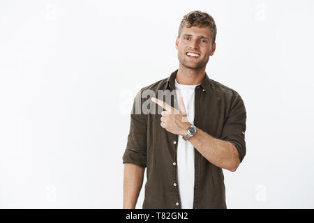 Guy showing us cool place inviting join. Friendly-looking sociable and carefree handsome masculine blond man with watch, bristle and blue eyes smiling - Stock Photo