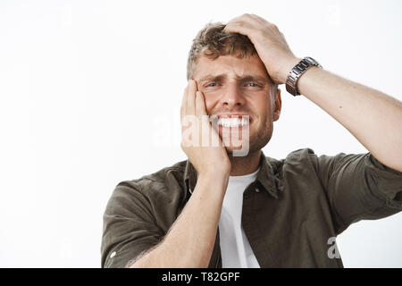 Close-up shot of man in agony and sorrow, feeling dismay and concern holding hands on head and face clenching teeth from painful feelings of regret - Stock Photo