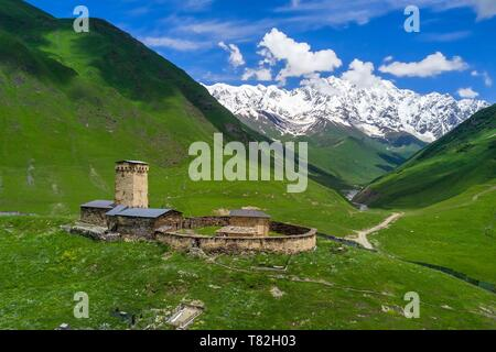 Georgia, Upper Svaneti (Zemo Svaneti), village of Ushguli, listed as World heritage by UNESCO, Lamaria St. Mary's church of Ushguli from the 12th century and Mount Chkhara (highest peak in Georgia with 5193 m) in the background (aerial view) - Stock Photo