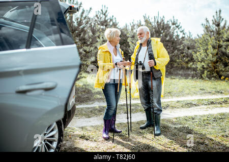 Senior couple in yellow raincoats standing near the car in the forest, enjoying their retirement