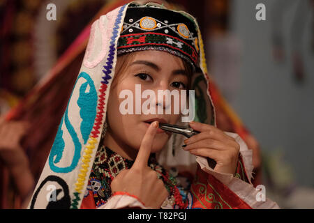 Young Uzbek woman wearing traditional embroidered costume in the Surkhandarya style playing jaw harp used by the Turkic peoples in the town of Jarkurgan in Surxondaryo Region in Uzbekistan - Stock Photo