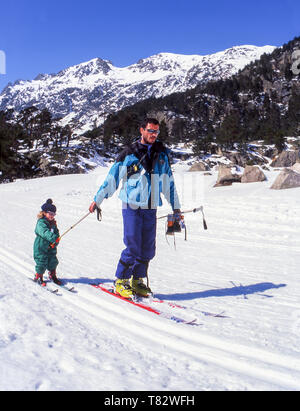 A father teaching his very young daughter how to ski The mountains of the department of Hautes-Pyrenees in Southwest France. - Stock Photo