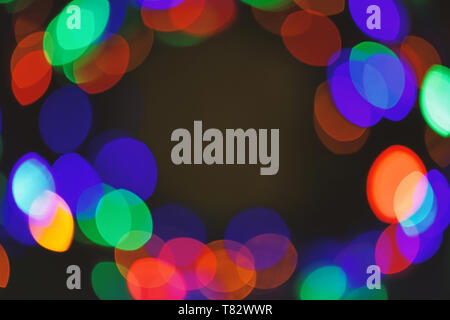 Defocused light of colorful garland. Festive backdrop with colorful lights. Bright and festive atmosphere of coming holiday. Abstract colorful bokeh background. Christmas decorations concept. - Stock Photo