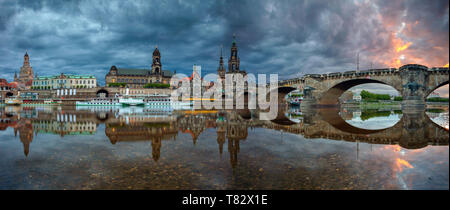 Dresden, Germany. Panoramic cityscape image of Dresden, Germany with reflection of the city in the Elbe river, during dramatic sunset. - Stock Photo