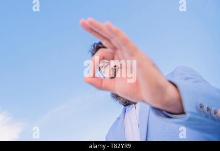 Guy looks through ok gesture close up. Excellent concept. Spying watching and observing. Man bearded businessman formal suit watching through fingers. I am watching you. Perfect gesture. - Stock Photo