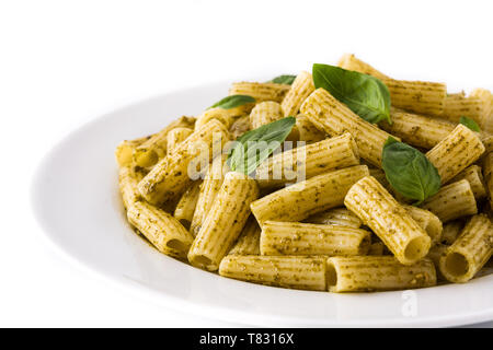 Penne pasta with pesto sauce and basil on a plate, isolated on white background - Stock Photo