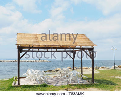 outside kiosk at the beach with two tables and plastic white chairs - Stock Photo