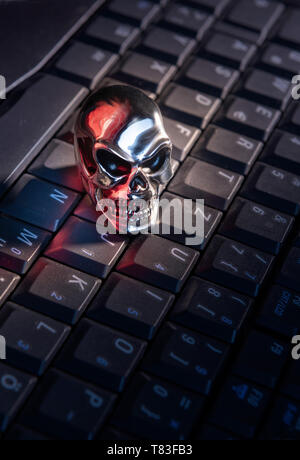 A skull made of shiny metal lies on a keyboard of a computer with strong red reflections