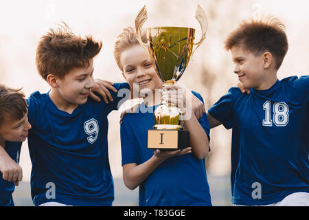 Boys sports team celebrating victory. Happy children holding golden trophy. Kids football team raising winners' cup.  Youth sports success - Stock Photo