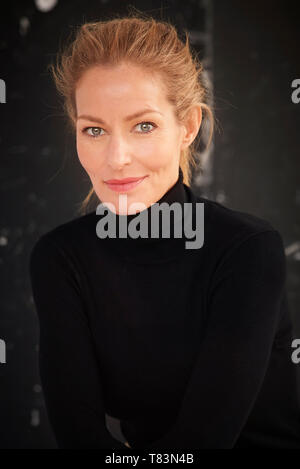 Close-up studio portrait of beautiful middle aged woman with blond hair wearing casual clothes while sitting at dark background. - Stock Photo