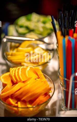 Orange, lemon and lime slices arranged on the glass bowl setting on holiday table. Focus on orange slices. - Stock Photo