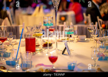 Jugs with lemonade and glasses on table at wedding party or banquet. Glasses and jugs with drinks setting on the festive table in restaurant. - Stock Photo