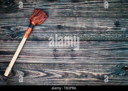 BBQ Mop or brush over top a rustic wood table / background with barbecue sauce on end. Image shot from overhead view. - Stock Photo