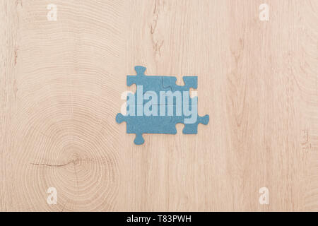 top view of blue puzzle pieces connected on wooden table - Stock Photo