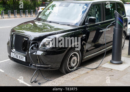 Charging an electric London taxi cab on the street. London, England