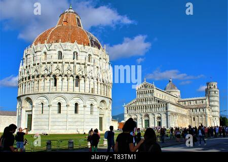 Tourists visiting the Baptistery, Cathedral and Leaning Tower of Pisa, Italy, October 2018.