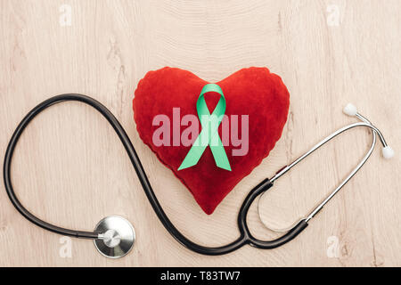 top view of toy heart, stethoscope and green ribbon on wooden background - Stock Photo