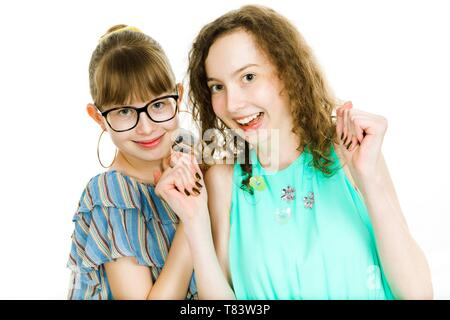 Two teenaged sisters posing together - shows happiness are smiling - white background - Stock Photo
