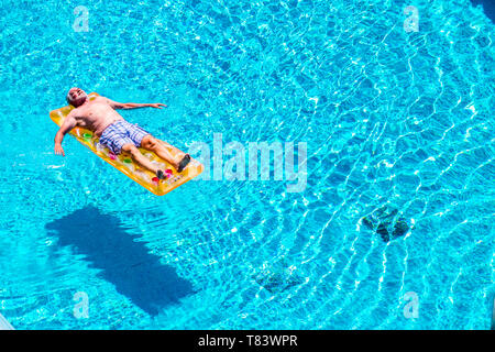 Senior aged man sleep and relax enjoying the blue water of swimming pool lay down on red watermelon lilo - summer vibes and retired lifestyle for cauc - Stock Photo