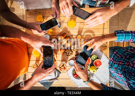 Morning breakfast table full of coffee and food viewed from top vertical above with group of people enjoying and taking pictures with mobile phones to - Stock Photo