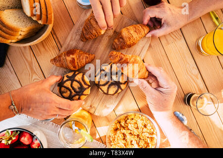 Group of friends family people viewed from vertical top view taking croissant and mixed food for breakfast morning activity - wooden table in backgrou - Stock Photo