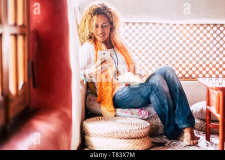 Fashion trendy attractive people young woman at home sitting and use mobile phone at home - hippy style clothes and coloured house - female and techno - Stock Photo