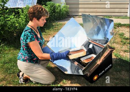 Woman baking fresh bread with farm-raised ingredients in a Sun Oven, cooking food with the heat from the sunlight, in Wisconsin, USA - Stock Photo