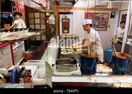 KYOTO, JAPAN - NOVEMBER 26, 2016: Restaurant chef prepares Japanese style okonomiyaki pancakes in Kyoto, Japan. - Stock Photo