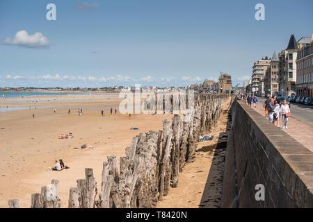 People walking along promenade at seafront. Saint Malo, Brittany, France - Stock Photo