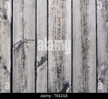 Close-up view to vertically oriented grey planks of old wooden garden table under the sunshine. - Stock Photo