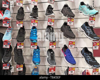 Running trainers on display at Sports Direct in Stratford upon Avon, Warwickshire, UK, on May 9, 2019. - Stock Photo