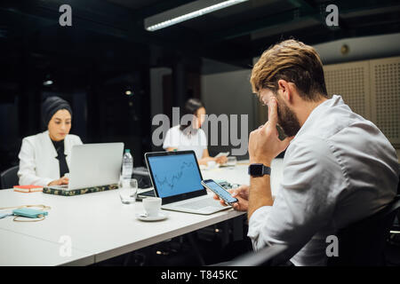 Businesswoman looking at laptop and smartphones at conference table